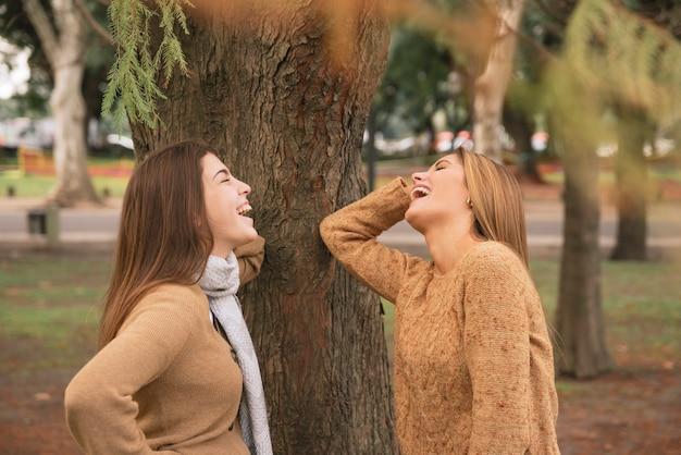 Middel van twee vrouwen wordt geschoten die in het park lachen dat Gratis Foto