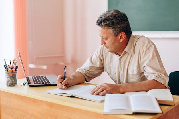 Middelbare leeftijd leraar aan tafel zitten en writtng. Premium Foto