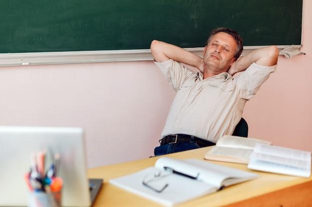 Middelbare leeftijd leraar hebben een rust in de klas en slapen. Premium Foto