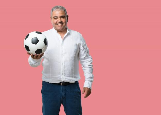 Middelbare leeftijd man glimlachend en gelukkig, met een voetbal, concurrerende houding, opgewonden om een spel te spelen Premium Foto