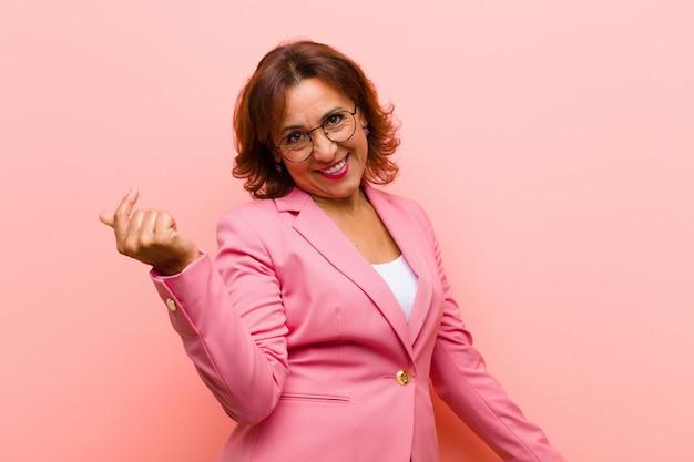 Middelbare leeftijd vrouw die lacht, zich onbezorgd, ontspannen en gelukkig voelt, danst en naar muziek luistert, plezier maakt op een feestje tegen roze muur Premium Foto