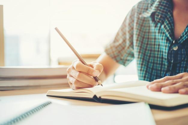 Middelbare school of hogeschoolstudent die in bibliotheek studeren en lezen Premium Foto
