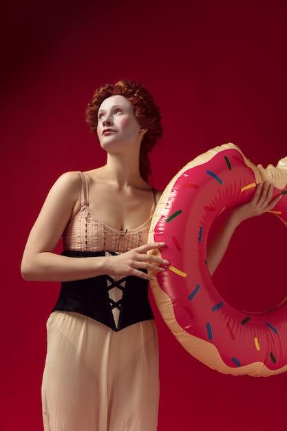 Middeleeuwse roodharige jonge vrouw als hertogin in zwart korset en nachtkleding staande op rode ruimte met een zwemcirkel als een donut Gratis Foto