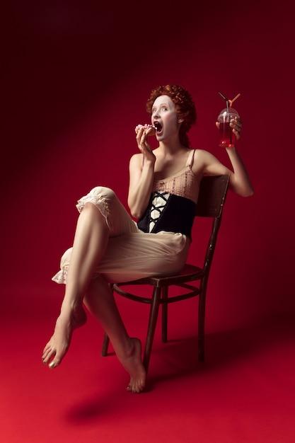 Middeleeuwse roodharige jonge vrouw als hertogin in zwart korset en nachtkleding zittend op een stoel op rode ruimte met een drankje en een donut Gratis Foto