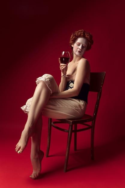 Middeleeuwse roodharige jonge vrouw als hertogin in zwart korset en nachtkleding zittend op een stoel op rode ruimte met een glas wijn Gratis Foto