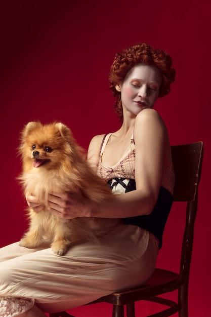 Middeleeuwse roodharige jonge vrouw als hertogin in zwart korset en nachtkleding, zittend op een stoel op rode ruimte met een kleine puppy of hond Gratis Foto