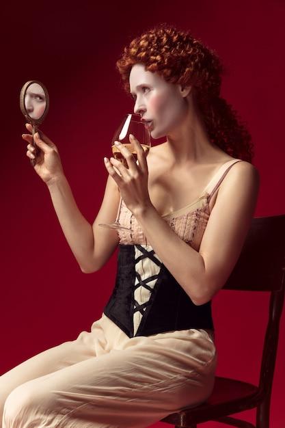 Middeleeuwse roodharige jonge vrouw als hertogin in zwart korset en nachtkleding zittend op rood Gratis Foto
