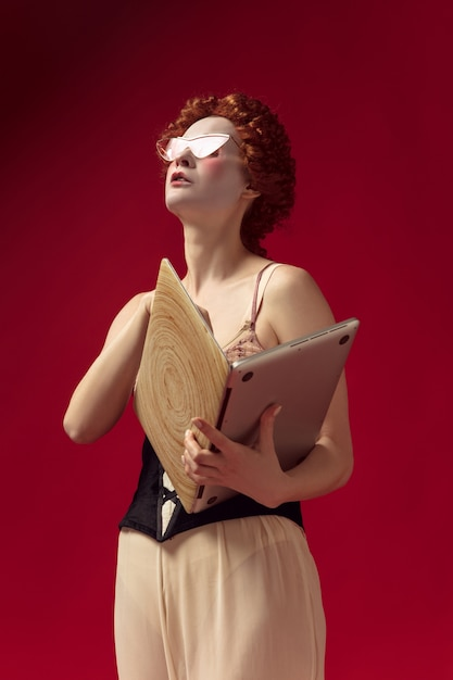 Middeleeuwse roodharige jonge vrouw als hertogin in zwart korset, zonnebril en nachtkleding staande op rode ruimte met een laptop als een boek Gratis Foto