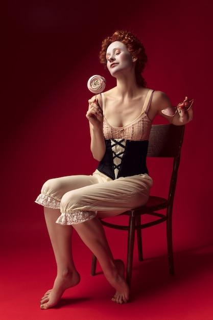 Middeleeuwse roodharige jonge vrouw als hertogin in zwart korset, zonnebril en nachtkleding zittend op een stoel op rode ruimte met een snoepje Gratis Foto