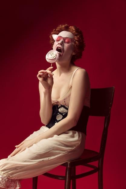 Middeleeuwse roodharige jonge vrouw als hertogin in zwart korset, zonnebril en nachtkleding Gratis Foto