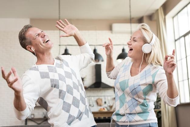 Middelgroot geschoten gelukkig paar met hoofdtelefoons binnen Gratis Foto