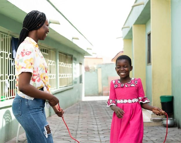 Middelgroot geschoten kind en vrouw met touwtjespringen Gratis Foto