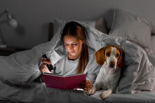 Middelgroot geschoten meisjeslezing met hond Premium Foto