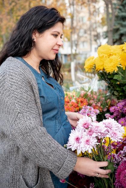 Middelgroot geschoten zwanger de bloemenboeket van de vrouwenholding Gratis Foto