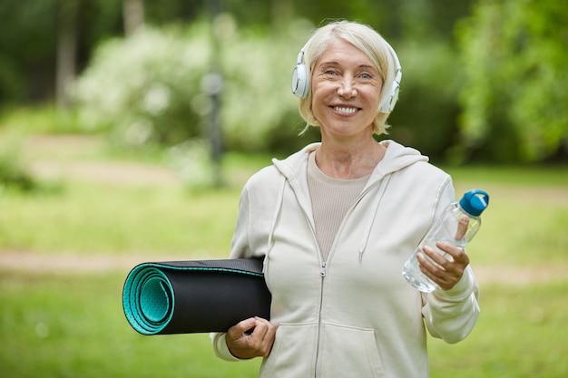 Middelgroot portret dat van gelukkige oude vrouw is ontsproten die witte hoofdtelefoons draagt die yogamat en fles water houden die bij camera glimlachen Premium Foto