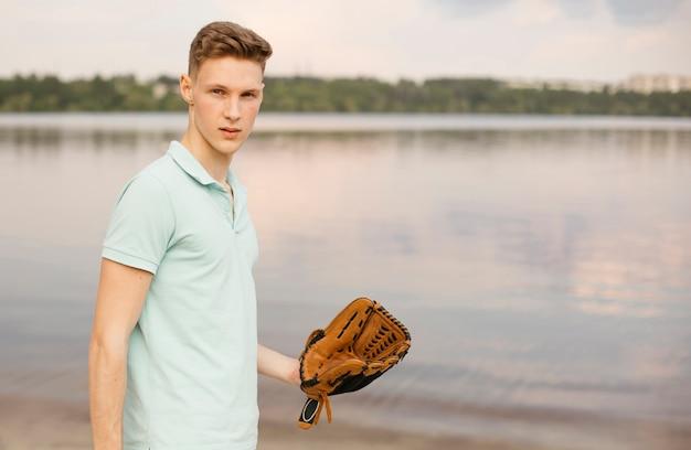 Middelgroot schot met honkbalhandschoen dichtbij het meer Gratis Foto