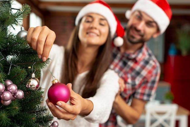 Middelgroot schot vaag paar dat de kerstmisboom verfraait Gratis Foto