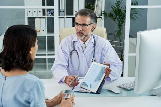 Middelgroot schot van arts op middelbare leeftijd die de diagnose via de tablet-pc verklaart Gratis Foto