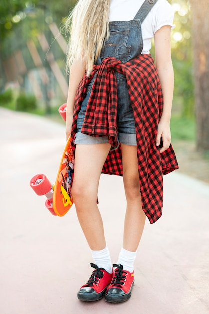 Middelgroot schot van blondemeisje met skateboard Gratis Foto