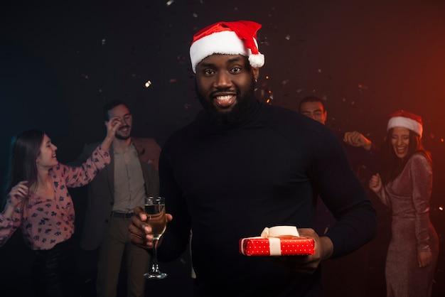 Middelgroot schot van glimlachende mens die champagne drinken bij nieuwe jarenpartij Gratis Foto