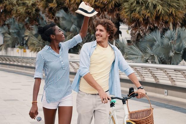Middelgroot schot van jong paar dat met fiets in de zomer loopt Gratis Foto