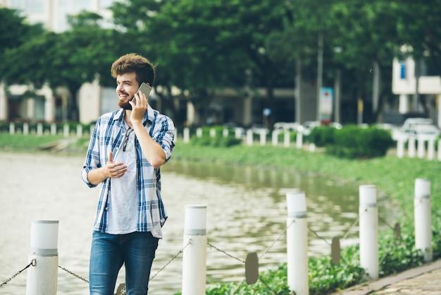 Middelgroot schot van jonge kerel die telefoongesprek maken die zich bij de bank van vijver bevinden Gratis Foto