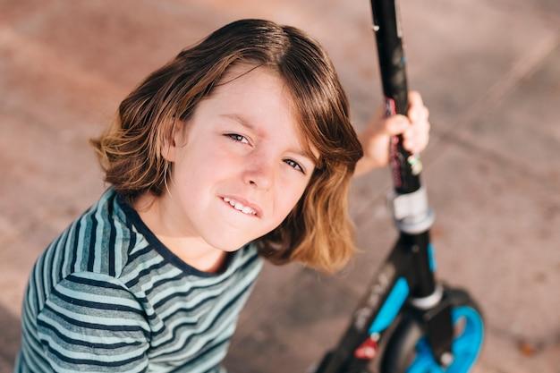 Middelgroot schot van jongen met autoped Gratis Foto