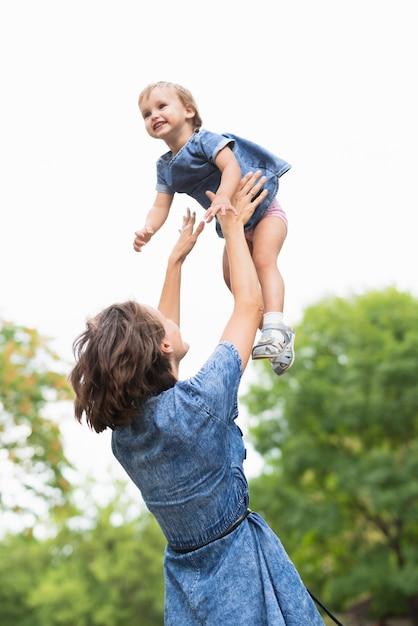 Middelgroot schot van moeder die haar dochter houdt Gratis Foto