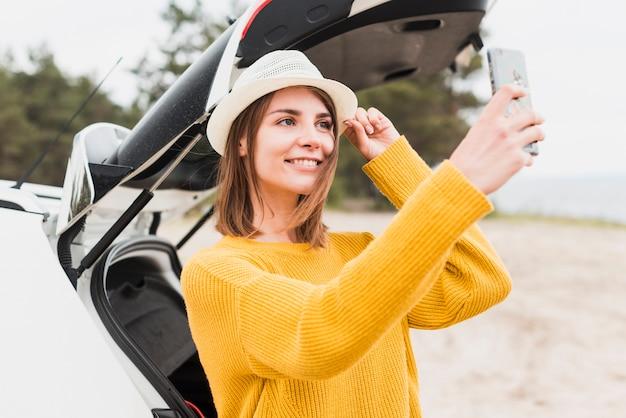 Middelgroot schot van reizende vrouw die een selfie nemen Gratis Foto