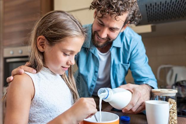 Middelgroot schot van vader die melk voor zijn dochter giet Gratis Foto