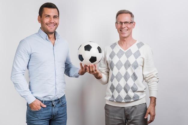 Middelgroot schot van vader en zoon die een voetbalbal houden Gratis Foto