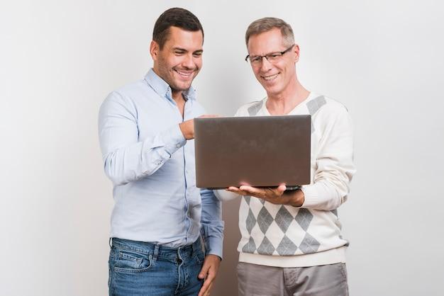 Middelgroot schot van vader en zoon met laptop Gratis Foto