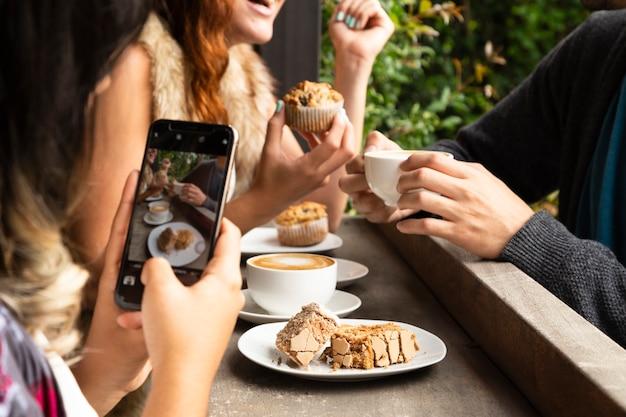 Middelgroot schot van vrienden bij koffiewinkel Premium Foto