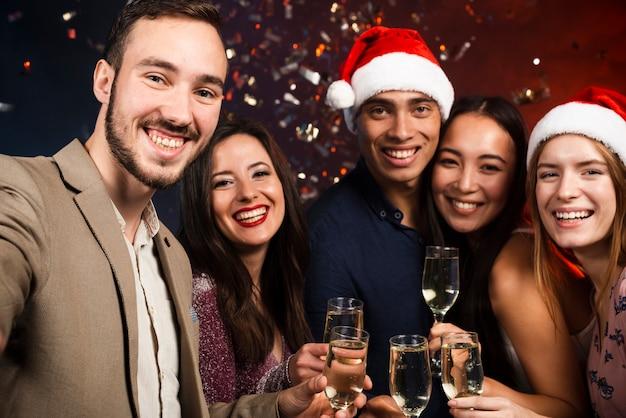 Middelgroot schot van vrienden op nieuwjaarsfeest met champagneglazen Gratis Foto