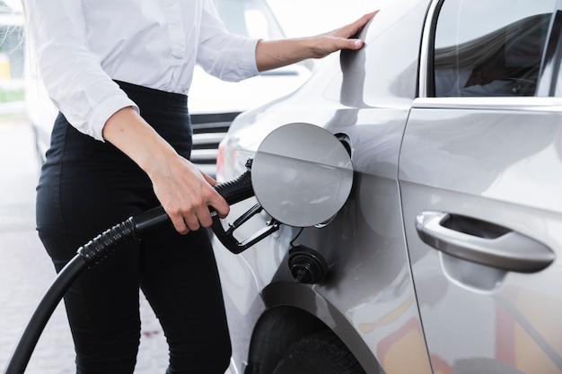 Middelgroot schot van vrouw die auto van brandstof voorziet Gratis Foto