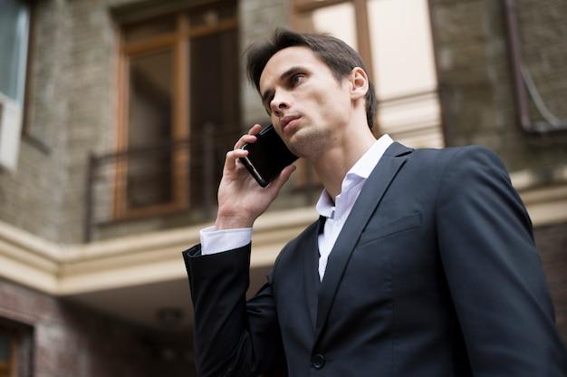 Middelgroot schot van zakenman die op telefoon spreekt Gratis Foto