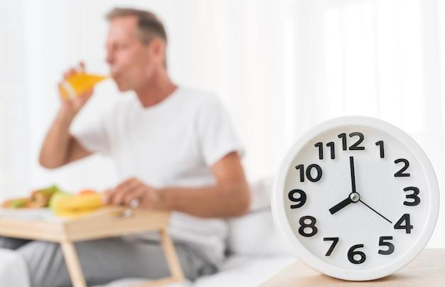 Middelgroot schot wazige man aan het ontbijt om 8 uur Gratis Foto