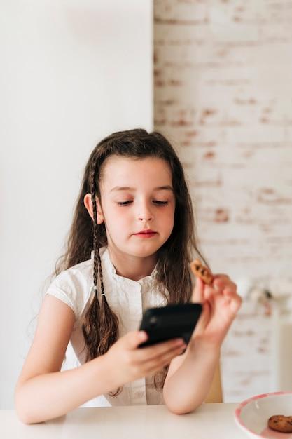 Middelgroot schotmeisje dat met telefoon koekjes eet Gratis Foto
