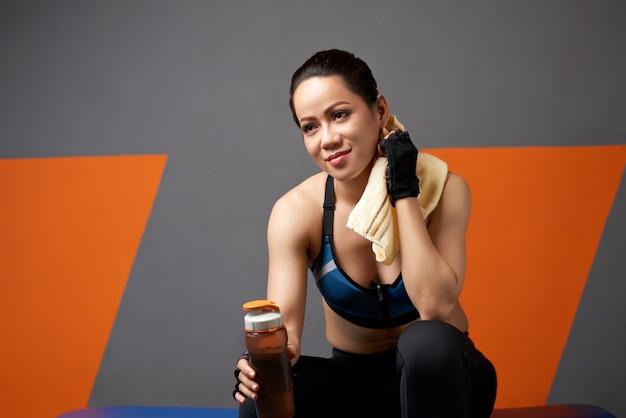 Middelgrote close-up van het sportieve meisje ontspannen na oefening met een fles water Gratis Foto