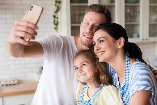 Middelgrote familie nemen selfie in de keuken Gratis Foto