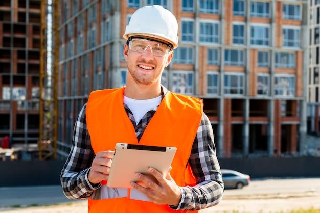Middelgrote geschoten bouwingenieur die tablet gebruiken Gratis Foto