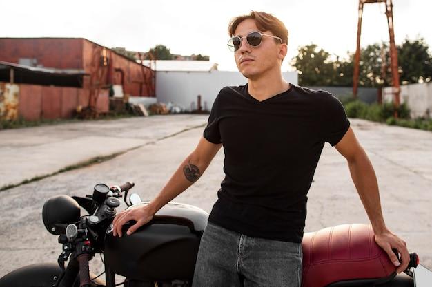 Middelgrote geschoten man die dichtbij motorfiets staat Gratis Foto