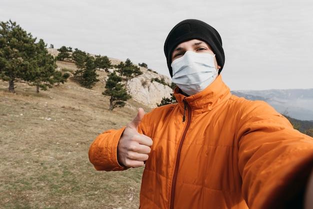 Middelgrote geschoten man die selfie met masker neemt Gratis Foto