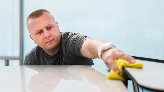 Middelgrote geschoten mens die auto met doek schoonmaken Premium Foto