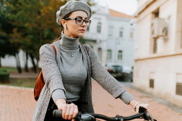 Middelgrote geschoten vrouw die de fiets berijdt Gratis Foto
