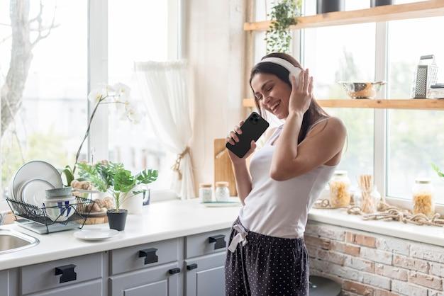 Middelgrote geschoten vrouw die hoofdtelefoons draagt Gratis Foto