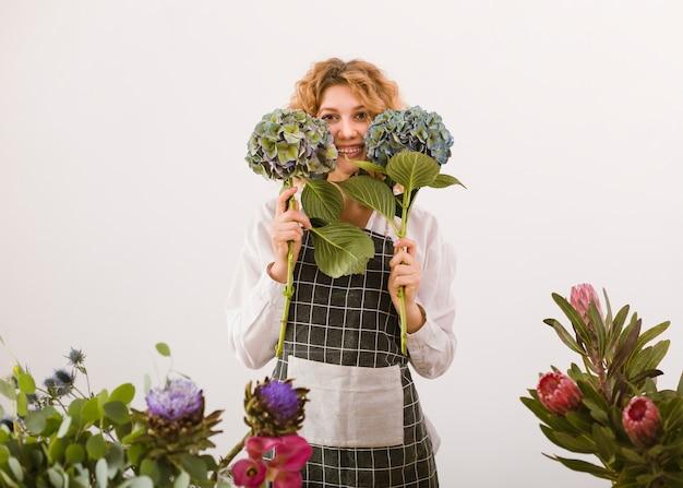 Middelgrote geschotene gelukkige bloemist die twee boeketten steunt Gratis Foto