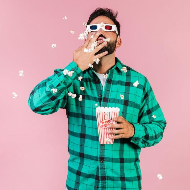 Middelgrote geschotene kerel die popcorn eet Gratis Foto