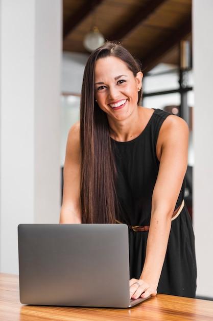 Middelgrote geschotene vrouw die en bij laptop glimlachen werken Gratis Foto