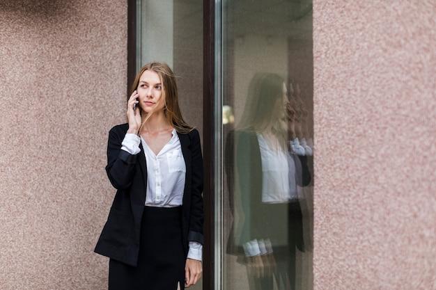 Middelgrote geschotene vrouw die op de telefoon door het venster spreekt Gratis Foto